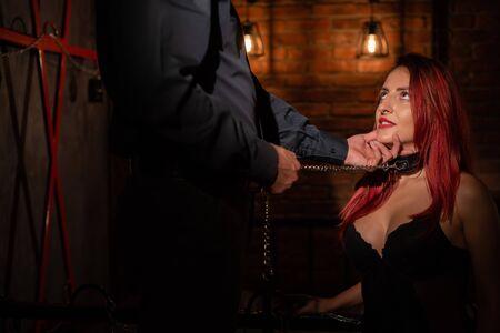 Cintura in pelle sul collo di BDSM. Petto di lusso in biancheria intima nera. Una donna si inginocchia davanti al suo partner nei giochi come una vittima. Giocattoli per adulti. Dito in bocca.