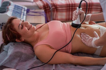 A woman lies on a couch and receives a hardware massage of the abdomen. The procedure for weight loss. Electric body massage.