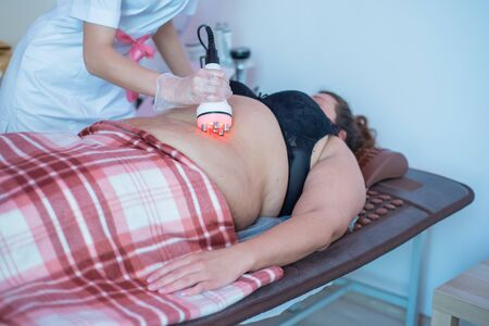 A fat woman lies on a couch and receives a hardware massage of the abdomen. The procedure for weight loss. Electric body massage.