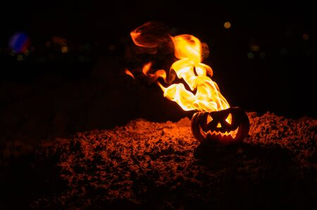 Tongues of flame in a pumpkin. jack-o-lantern on fire on a black background. Halloween symbol on the ground. Trick or treat. Close up.