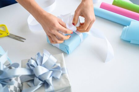 Woman wraps boxes with gifts for the new year. Female hands close-up. Prepares a surprise for mothers day. Wrapping paper and ribbon for birth. The designer is tying a bow.