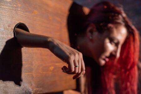 Una donna dai capelli rossi è imprigionata in una gogna di legno durante i giochi. BDSM Fantasie erotiche.Subordinazione. Giocattoli per adulti.