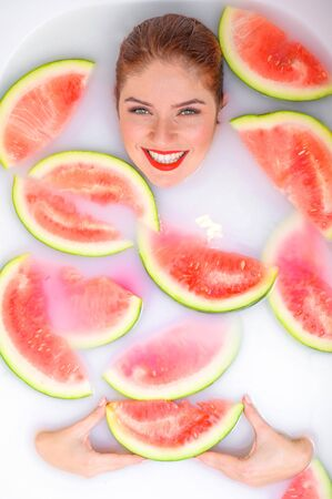 Portrait of a beautiful red-haired woman takes a bath with milk and slices of watermelon. Spa treatment for skin rejuvenation and nutrition. Ripe slices of the largest berry. Banque d'images
