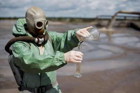 A male environmentalist in a green protective suit and gas mask takes a sample of water. The scientist is doing a toxicological study. Post apocalypse.