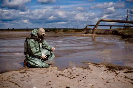 A male environmentalist in a green protective suit and gas mask takes a sample of water. The scientist is doing a toxicological study. Post apocalypse Banque d'images - 133947132