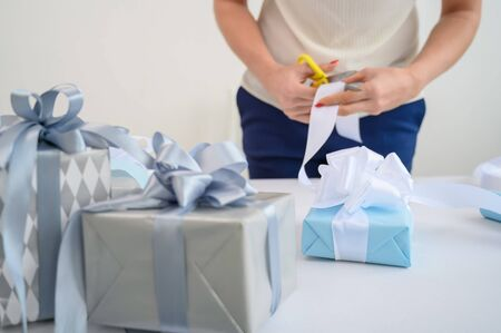 Woman wraps boxes with gifts for the new year. Female hands close-up. Prepares a surprise for mothers day. Wrapping paper and ribbon for birth. The designer is tying a bow
