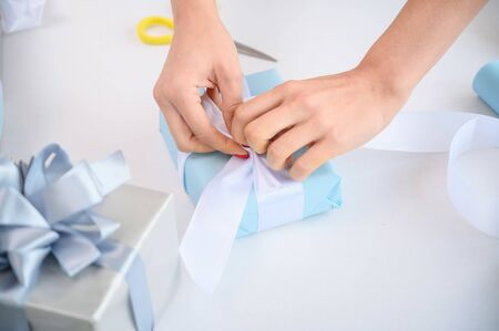 Woman wraps boxes with gifts for the new year. Female hands close-up. Prepares a surprise for Christmas. Wrapping paper and ribbon Stock Photo