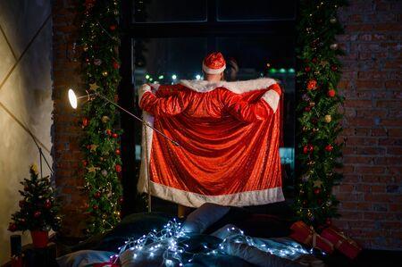 Humorvolles Bild eines Mannes in einem Anzug von Santa Claus, der Striptease am Fenster zeigt. Der böse Weihnachtsmann öffnete seinen Anzug für einen Scherz. Vulgärer Humor.