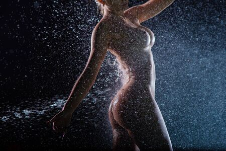 Naked female figure in the shower. Wet Woman without clothes with a beautiful figure under the streams of water. Trickling down his bare chest and a perfect ass female. Standard-Bild - 134475970