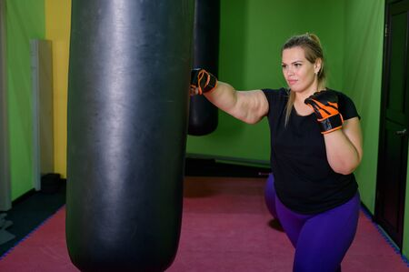 A fat woman is training kickboxing in the gym. A girl in boxing gloves beats a punching bag. Female obesity. Hard workouts for weight loss.