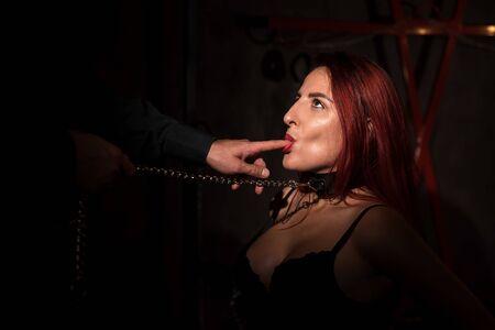 Retrato de una mujer durante juegos de rol. Una chica encadenada está encadenada delante de su amante y le lame los dedos. Un hombre toca a su amante por la cara.