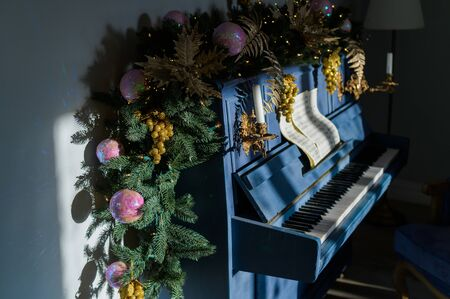 Close-up Christmas decoration on blue grand piano. Happy new year. The spruce branch lies on the piano.