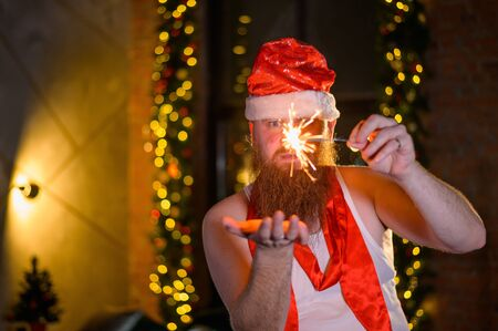 Santa with christmas sparkles. A man with a red beard in a hat of Santa Claus mimics women. Banco de Imagens