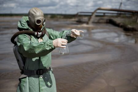 A scientist takes a sample of water from a river after the release of chemical waste. A man in a respirator and a green protective suit from radiation. Water analysis experts. Ecological catastrophy.