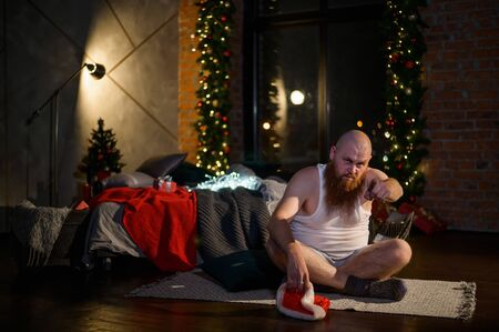 Humorous image of a man without pants in front of Christmas. Bald Santa Claus with a red beard unpacks a gift. A parody of a glamorous womens New Year photo shoot. Joke.