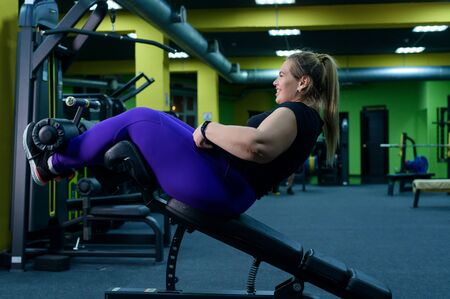 Fat woman trying to lose weight and doing bench press exercises on the press bench in the gym. Overweight blonde is engaged in fitness.