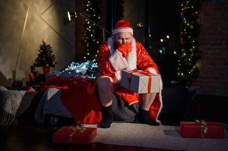 Bad evil Santa Claus with a red beard sits on the bed and collects gifts on Christmas Eve. A man in a suit of Santa Claus before the New Year. Stock Photo