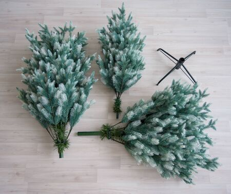 Close-up of pieces of artificial Christmas tree. The process of collecting and decorating the tree for the new year. View from above. Compound reusable spruce. Decoration for the holiday.