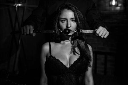 Un hombre domina y pone una mordaza en la boca de su pareja. Concepto BDSM. Retrato de una mujer en ropa interior seductora con un juguete íntimo en la boca. Pareja sexy juega juegos de amor. Foto de archivo