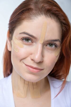 Portrait of a redhead woman with tapes on skin color face for rejuvenation. An alternative way to fight wrinkles.