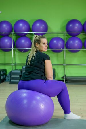 A fat woman is engaged in the gym and trying to lose weight. An obese girl sits on a fitness ball.