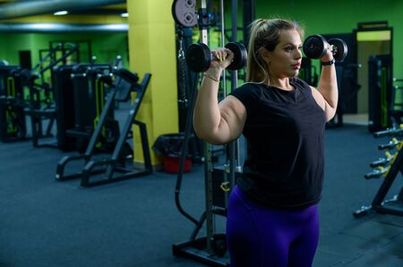 An obese woman is working on losing weight. Fat blondes train biceps with a dumbbell in the trainer room. A lot of excess weight due to poor eating habits and lack of self-control. Stock Photo