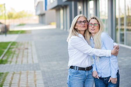 A beautiful blonde with glasses and her elderly mother are walking together. Mothers Day. Beautiful aged woman is a senior citizen and her adult daughter. Happy women of different generations.