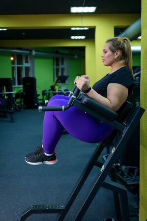 An obese woman is doing exercises on the abdominal muscles for weight loss. Fat blonde is engaged in a simulator in the gym. Stockfoto