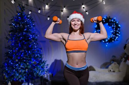 Sporty woman in santa claus hat stands posing with dumbbells in her hands. Female bodybuilder exercises for biceps on the background of the Christmas tree.