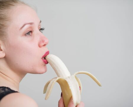 A girl with long blond hair sexually licks a big yellow banana with her tongue. Is oral sex