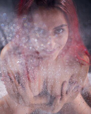 La femme rousse prend une douche. Une fille la couvrant de ses mains se tient derrière un verre embué.