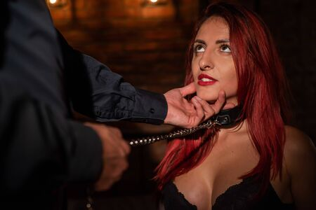 Portrait of a woman during role-playing games. A girl in fetters is in fetters in front of her lover and licks his fingers. A man touches his mistress by the face. 스톡 콘텐츠
