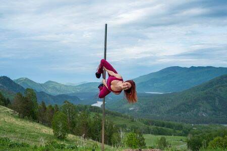 Beautiful red-haired woman dancing on a portable platform on a background of mountains. The girl moves sexually next to the pole. Jumpsuit for classes. high heels. Altai. Awesome flexibility. Imagens