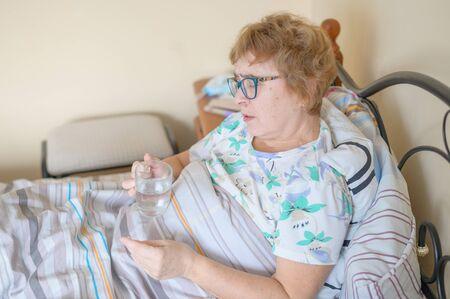 Chora stara kobieta leży w domu w łóżku. Emeryt leczy się z choroby i wypija szklankę wody.