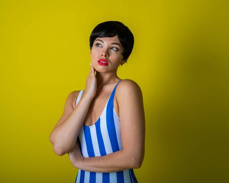 Brunette in a striped swimsuit posing in the studio on a bright yellow background. Woman in a short wig with sensual lips. Zdjęcie Seryjne