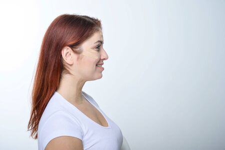 Profile red-haired woman with tape on the skin complexion rejuvenation. An alternative way to fight wrinkles. 版權商用圖片
