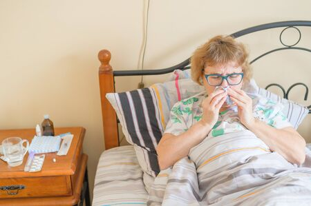An elderly woman suffers from the flu and runny nose. The pensioner blows her nose in the nasal raft.