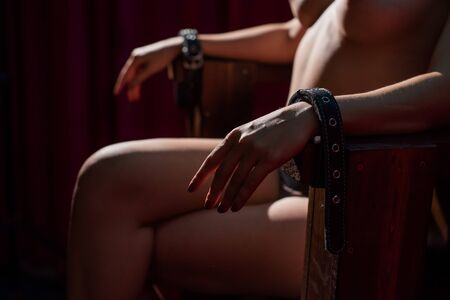 Unrecognizable nude woman sitting on a wooden chair chained with leather handcuffs. A girl without a face as a victim. BDSM Banco de Imagens