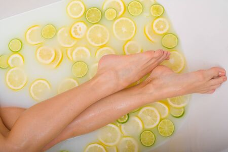 Unrecognizable woman takes a milk bath with lemons and limes. Citrus spa. Body care. Skin whitening. Female legs top view