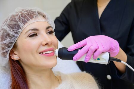 Portrait of a middle-aged woman receiving a non-surgical rejuvenation procedure at a cosmetologist. RF face lifting. Hardware facial massage. Stockfoto