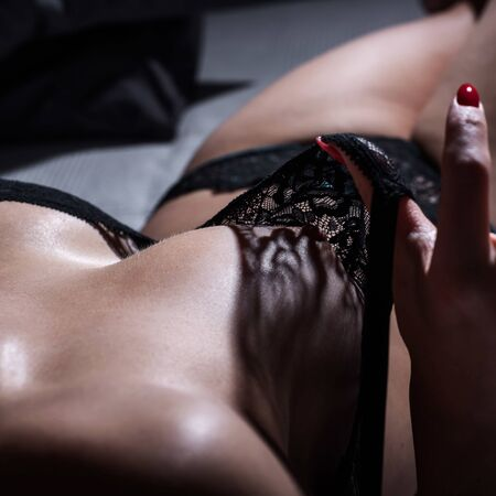 The unrecognized woman erotically pulls a black lace bra with a beautiful silicone breast. Close-up of female boobs.