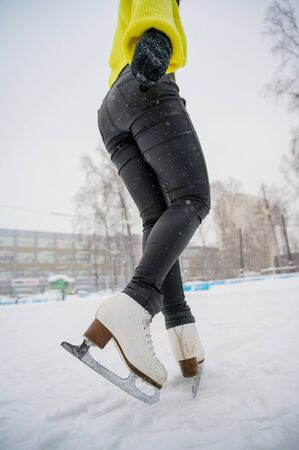 Figure skating on the street at an outdoor ice rink. Close-up of the skaters legs on ice. A woman goes in for sports Stock Photo