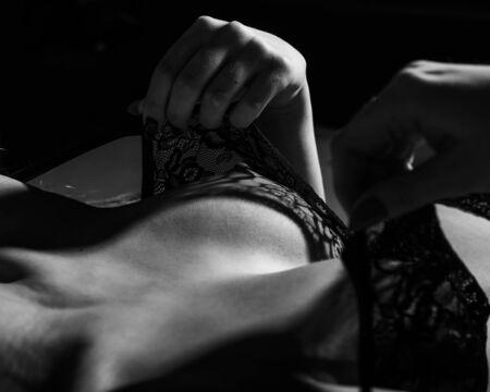The unrecognized woman erotically pulls a black lace bra with a beautiful silicone breast. Closeup of female boobs in seductive underwear. Monochrome.