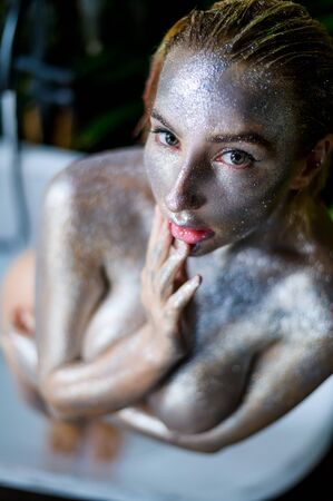 Portrait of a young beautiful woman with very big in silver paint. Naked girl with sparkles of metallic color on the skin.