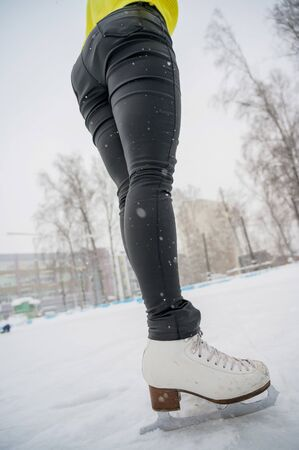 Figure skating on the street at an outdoor ice rink. Close-up of the skaters legs on ice. A woman goes in for sports.