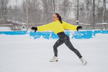 Professional skater on an outdoor ice rink. A woman on knees is preparing a solo program for the competition.