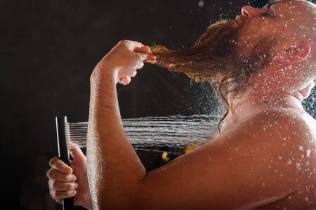 The bald guy takes a shower. A brutal man with a red beard is standing in the bathroom under a stream of water and washes. Spray scatter on a black background.