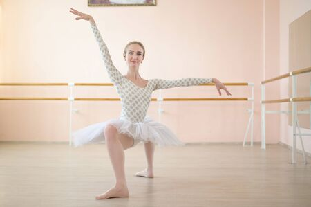 A very flexible ballerina in a tutu stands in a plie in a class with ballet machines. Incredibly Plastic Dancer.