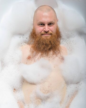 Portrait of a bald man fooling around in the foam bath. Top view on guy having fun in the bathroom.