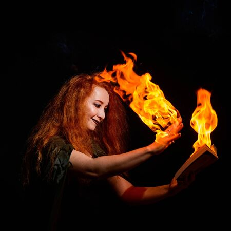 An ominous witch sets her spell book on fire with the power of thought. Red-haired woman conjures for Halloween. Flames on the hands.